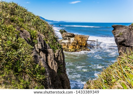 """Scenic coastline, powerful surf, stones and rocks. Pancake Rock is a natural wonder of Paparoa National Park, New Zealand. Stone flat """"pancakes"""". The concept of ecological, active and phototourism"""