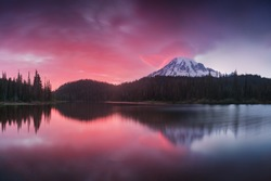 Scenic view of Mount Rainier reflected across the reflection lakes.. Pink sunset light on Mount Rainier in the Cascade Range, Washington State. Beautiful Paradise area