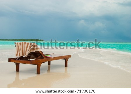 Scenic view of sun lounger on sandy tropical beach by idyllic turquoise sea, Maldives.