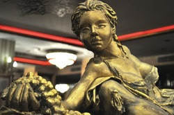 sculpture of a woman in bronze holding grapes