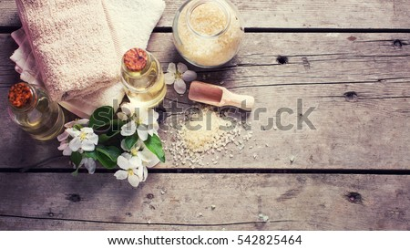 Sea salt, towels, aroma oil in bottles and flowers on  vintage  wooden background. Selective focus. Flat lay with copy space. Toned image.