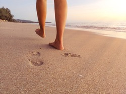 Sea trip - Woman walking on the sand, leaving footprints in the sand. At Krabi, Thailand In the summer morning