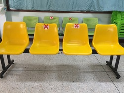 4 seats waiting row chairs crossed sign applied for people to keep social distancing ,prevent coronavirus or Covid-19 that is spread  around the world in Thailand
