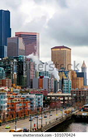 Seattle waterfront with colorful buildings under a cloudy sky