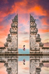 (Selective focus) A girl is jumping in front of the Gate of Heaven with its reflection in the water during a stunning sunset. Bali, Indonesia.