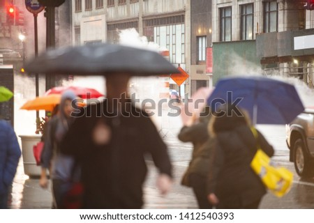 (Selective focus) Blurred people with umbrellas are crossing the 42nd street in Manhattan. Steam coming out from from the manholes in the background. Manhattan, New York City, Usa. stock photo