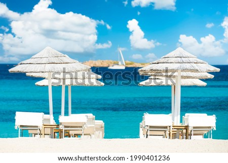 (Selective focus) Stunning view of some white thatch umbrellas and sunbeds on a white sand beach bathed by a beautiful, turquoise sea. Romazzino Beach, Porto Cervo, Sardinia, Italy. Photo stock ©