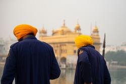 (Selective focus) Two security guards, wearing the Dastar, are walking in front of the  Golden Temple during the covid-19 pandemic. Amritsar, Punjab, India.