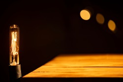 (Selective focus) Vintage light bulb on empty wooden table illuminated by a warm light, black background with a blurred light chain. Empty wooden board with copy space.