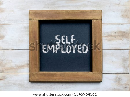 """""""Self Employed"""" written in chalk writing on a simple blackboard sat on white washed wood"""