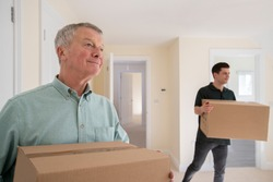 Senior Man Downsizing In Retirement Carrying Boxes Into New Home On Moving Day With Removal Man Helping