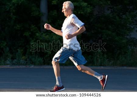 senior man running in the summer park