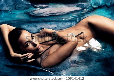 sensual naked  woman enjoy in natural pool of blue stone