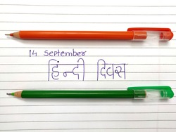 14 September hindi divas concept with orange and green pen on book's paper. Translate: