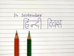 14 September hindi divas concept with orange and green pen on book's paper Translate 'Hindi divas'