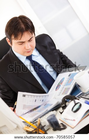Serious business man sitting at office desk and working  with financial documents
