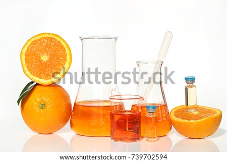 Serum with vitamin C in ampoules.  vitamin c in glass laboratory bottles, orange in a cut . Vitamins concept. Organic vegan cosmetics for beauty and health.