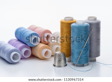 Set of multicolored threads on reels,  large needle for sewing and  thimble. - Shutterstock ID 1130967314