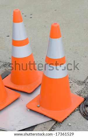 Set of orange and white traffic cones on the ground