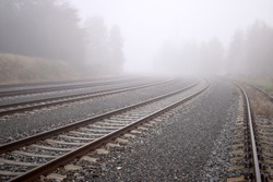 Several train rails ending in fog