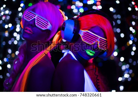 2 sexy cyber glow raver women filmed in fluorescent clothing under UV black light