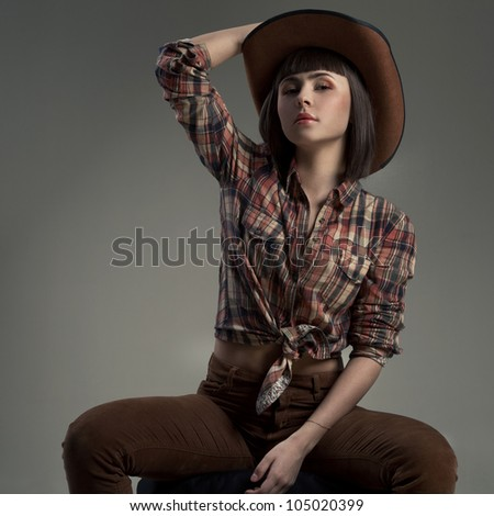 sexy woman in a hat  in an image of the American cowboy