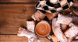 Sfrappole or chiachiere or angel wings and aromatic coffee on a woody background. Carnival food TYPICAL and carnival mask. Traditional sweet crisp pastry deep-fried and sprinkled with powdered sugar.