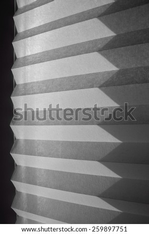 shadow in the shape of triangles from paper blinds on the wall, streaks of light and shadow, abstract background