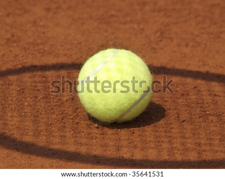 Shadow of a tennis racket on a ball on clay