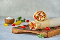 Shawarma with chicken  and garlic sauce on wooden board. Closeup