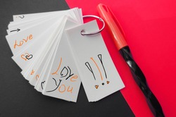 sheets Notepad are held together with metal ring , mockup, pen and black red background . lettering love you and simple teenage  sketches about love