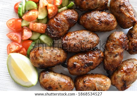 Sheftalia : Cypriot Lamb and Pork Sausages.  Grilled Sausages with Fresh Vegetables (Cucumber and Tomato) on a White Plate. Traditional Cypriot food.  Foto stock ©
