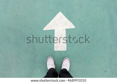 shoes standing on the concrete floor and white direction sign to go ahead
