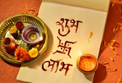 'Shubha Labha' (Prosperity and Profit) written in Hindi script on the notebook, arranged along with diwali puja. It is a tradition for businesses to start accounting with new account books on Diwali.