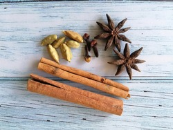 4 siblings that is cinnamon, cloves, star anise and cardamom pods on wooden table.