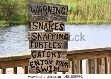 sign listing the dangers of swimming in Florida waters                              #1481805992