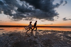 silhouette of a couple in love who runs along the beach against the backdrop of a beautiful sunset and clouds. A wonderful romantic landscape for a love story