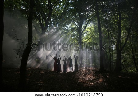 silhouette of a group of women who reach for the light in a dark forest with smoke