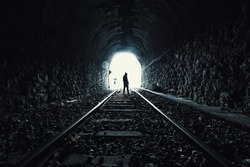 silhouette of a person coming out of an abandoned tunnel