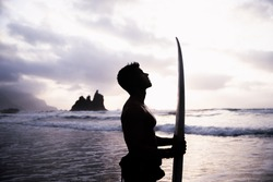 Silhouette of a surfer at the beach with surfboard in hand looking to the sky. Person in contact with nature, Focused sportsman
