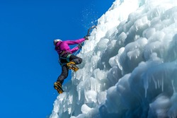 Silhouette of a woman with ice climbing equipment, hiking at a frozen waterfall, swinging the ice axe