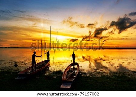 silhouette of children on wood boat at sunset