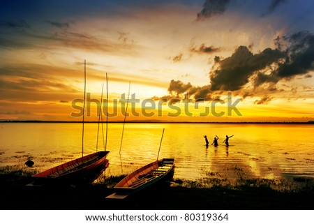 silhouette of children on wood boat at sunset, thailand