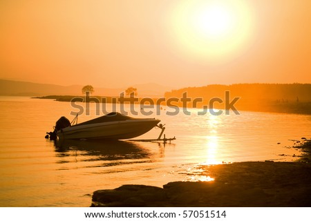 silhouette of single motor boat at sea off the coast on the background of  beautiful red sunset - stock photo