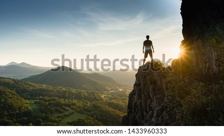 Silhouette of the person on the high rock at sunset. Satisfy hiker enjoy view. Tall man on rocky cliff watching down to landscape. Vivid and strong vignetting effect.