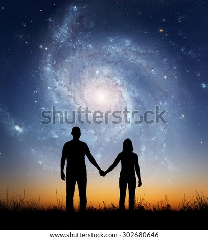 Silhouette of young couple under stars. The concept on the theme of love. Elements of this image furnished by NASA.
