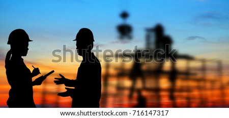 silhouette portrait of engineer Work order in construction site on blurry colorful light sunset.