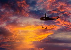 silhouette soldiers in action rappelling climb down from helicopter with military mission counter terrorism assault training on sunset