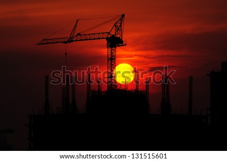 Silhouettes Office buildings construction site and crane with the sunset