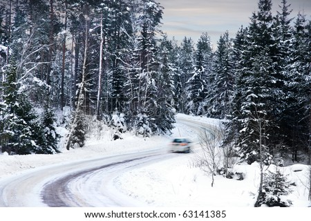 single car driving along a a winter road
